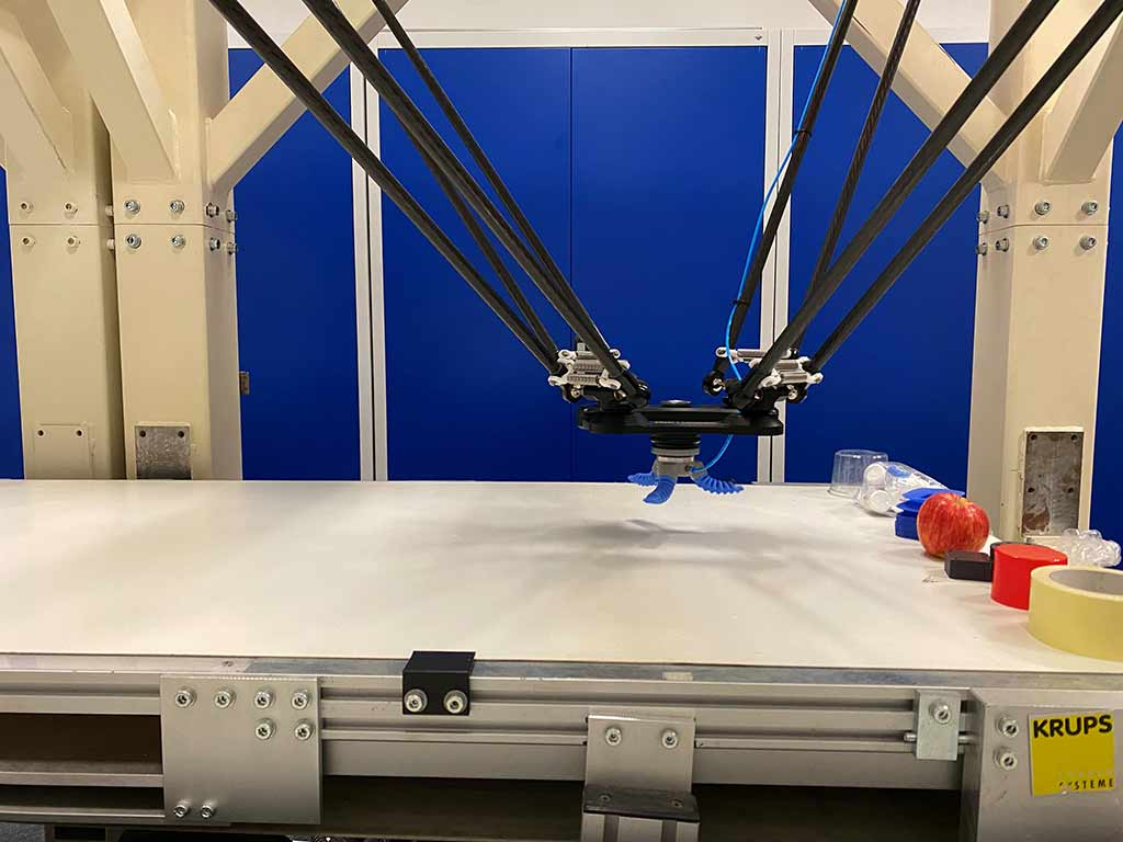 Omron delta robot handling several objects with 3 claw gripper